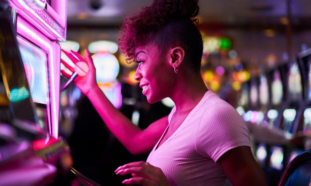 happy woman gambling at casino playing slot machine